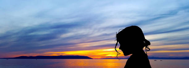 silhouette of a young girl with sunset over the adriatic sea in background - makarska, croatia - hair line surface stock photos and pictures