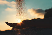 Silhouette of a young girl's hand pouring sand from a beach against a blue sky at sunset