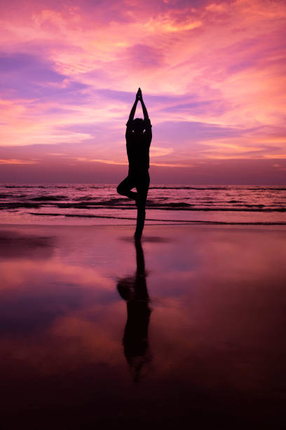 Silhouette of a young man meditating at sunset stock photo
