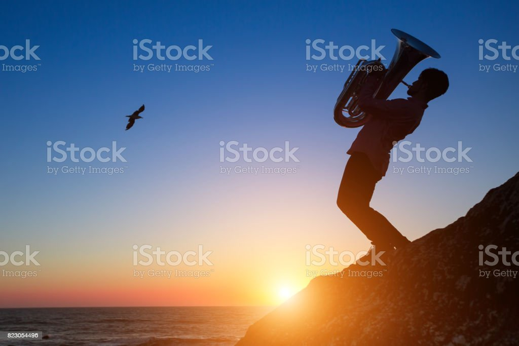 Silhouette of a young man playing the trumpet on rocky sea coast during amazing sunset. Tuba instrument. stock photo