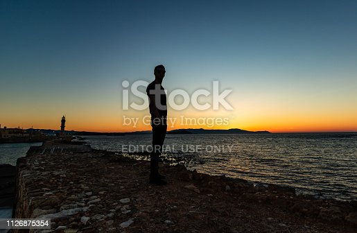Chania, Greece - 2019. Silhouette of a young tourist looking over the olf venetian harbor of Chania in Crete at sunset.