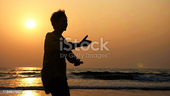 Silhouette of active senior woman practicing tai chi gymnastic on sandy beach at sunset.