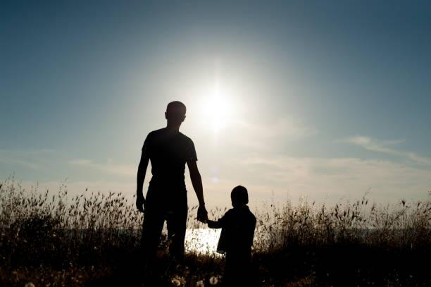 silhouette d'homme adulte et petit garçon en toile de fond le coucher du soleil de la mer - nuage 6 photos et images de collection