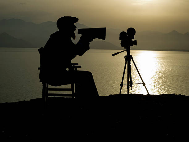 Silhouette Of Adult Man Directing Film In Outdoor Movie Set stock photo