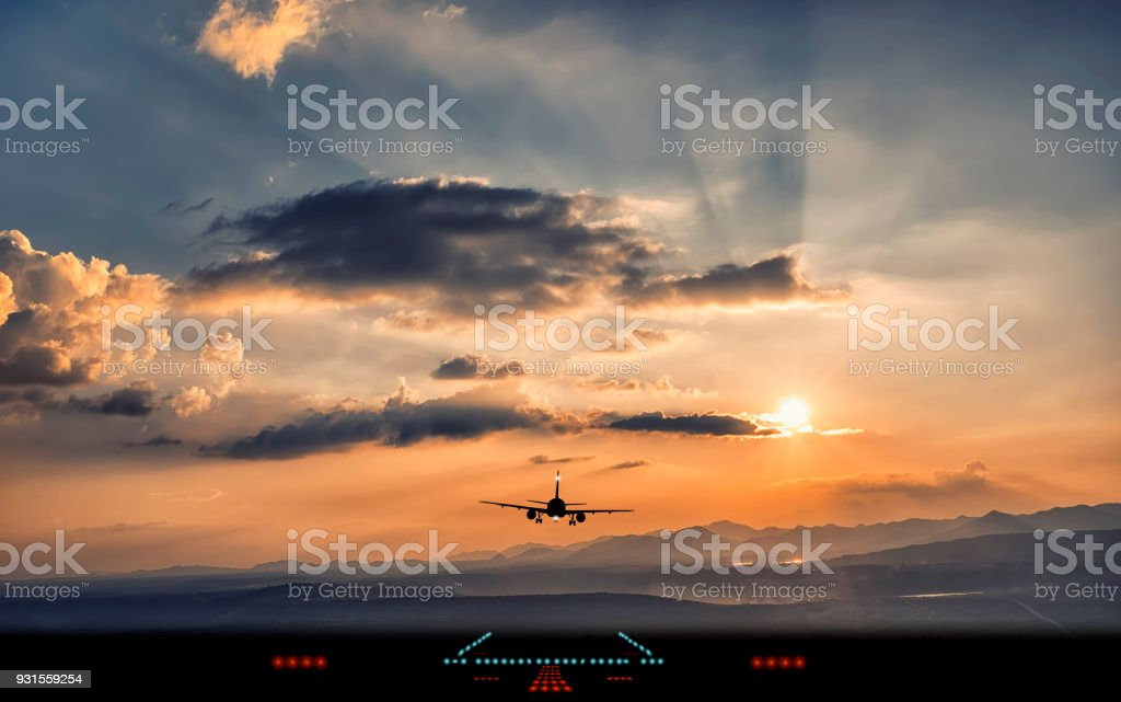 Silhouette of airplane landing to airport runway with beautiful sunset light stock photo