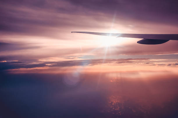 Silhouette of airplane wing flying above the cloud with sunlight rays in sunset or sunrise beautiful pink pastel sky stock photo