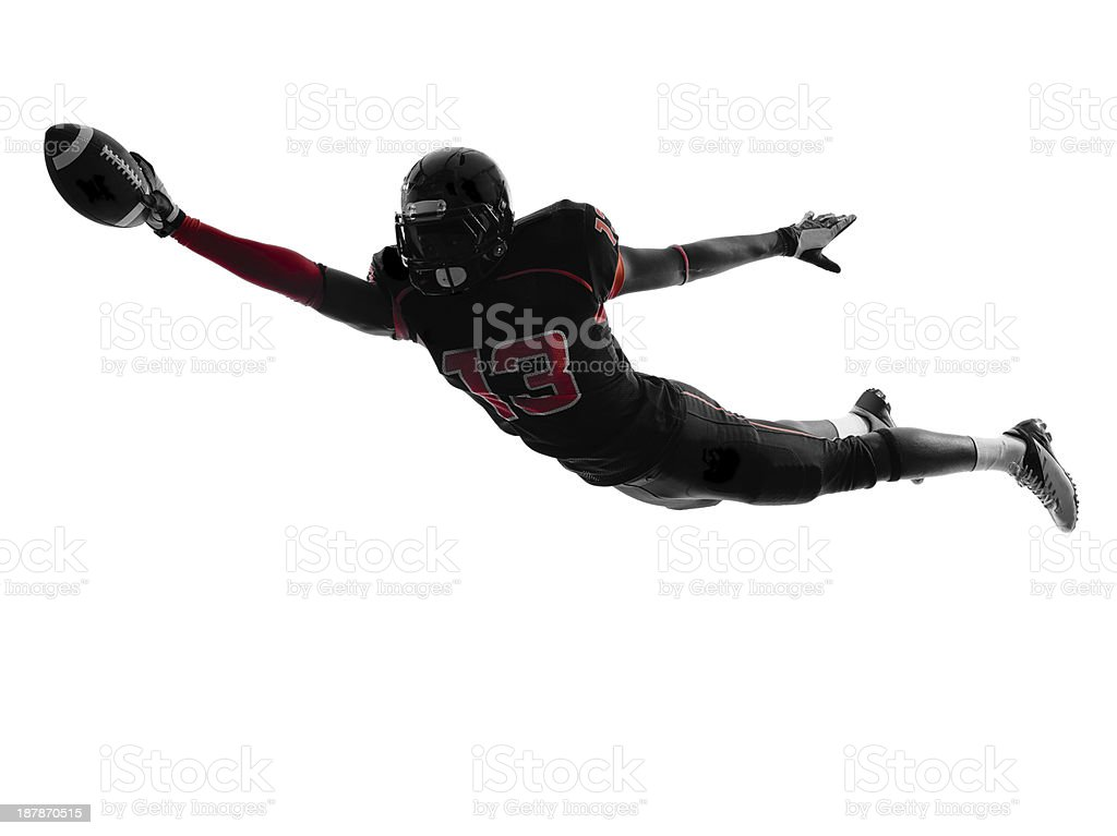 Silhouette of American football player scoring touchdown stock photo