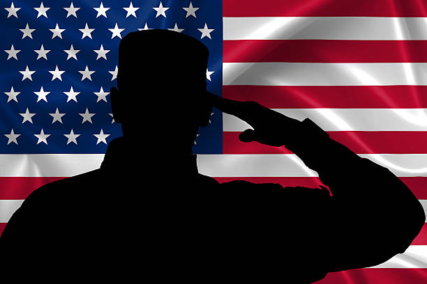 silhouette of american (usa) soldier saluting to usa flag - saluting stock photos and pictures