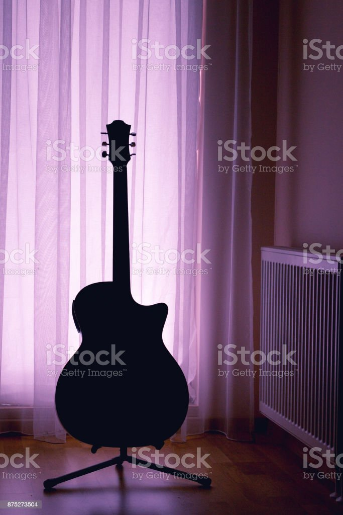 silhouette of an acoustic guitar on a light background of curtai stock photo