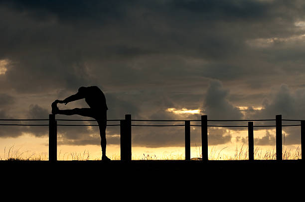 silhouette of an athlete stretching at dusk stock photo
