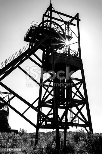 Silhouette of an Decaying, old, pit-head in South Wales. Black and white image with a specular starburst showing the stark death of a once vibrant industry and community.