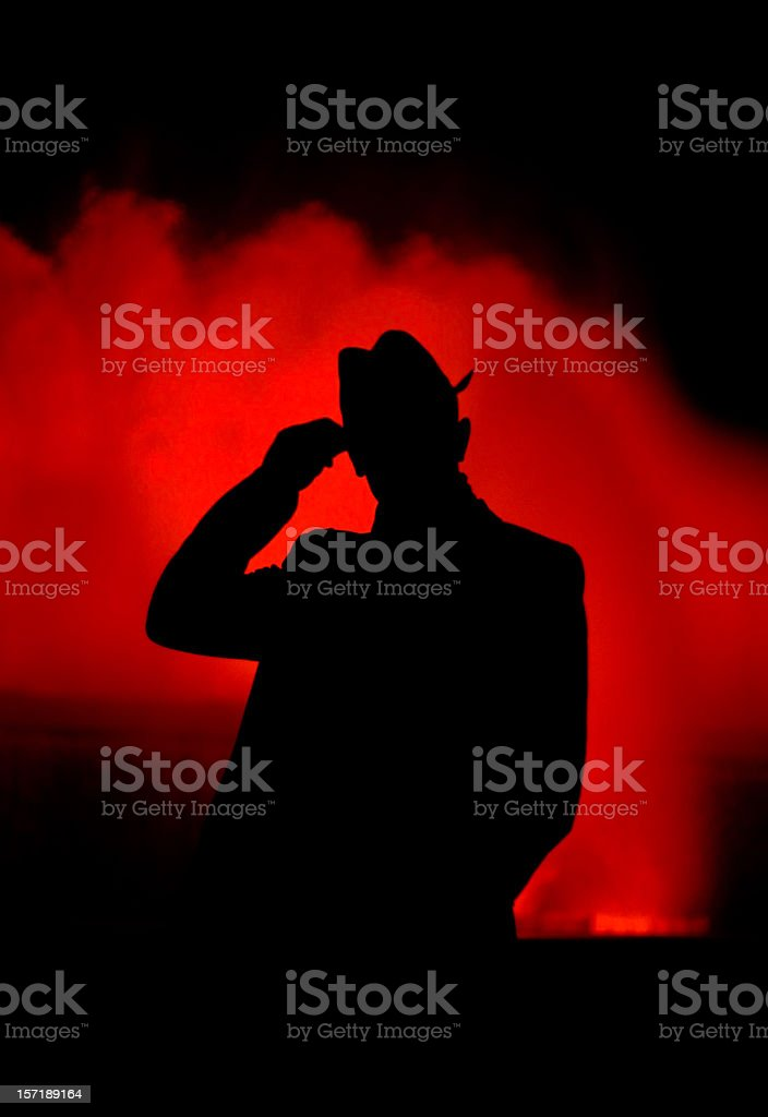 Silhouette of an elegant man against colorful fountain at night. stock photo