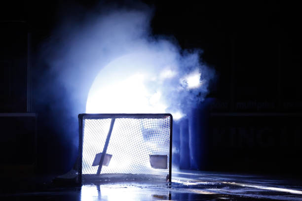 A silhouette of an ice hockey goal in front of illuminated player entrance. stock photo
