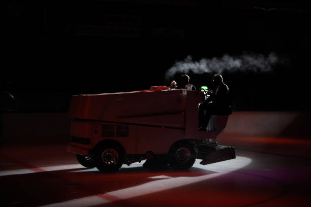 A silhouette of an ice maintenance vehicle preparing the ice surface during game break. stock photo