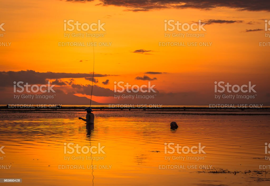 Silhouette of an indonesian fisherman with his long rod, - Royalty-free Adult Stock Photo