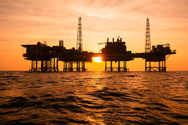 Silhouette of an offshore oil installation - foto de acervo