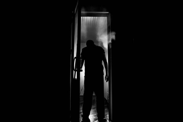 silhouette of an unknown shadow figure on a door through a closed glass door. the silhouette of a human in front of a window at night. scary scene halloween concept - kaukaz południowy zdjęcia i obrazy z banku zdjęć