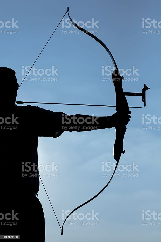 Silhouette of archer ready to discharge the arrow stock photo