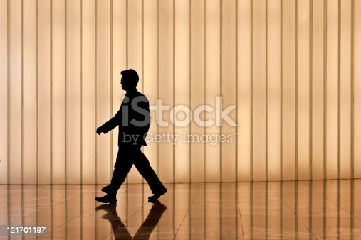 905689676 istock photo silhouette of asian business man against modern light wall 121701197
