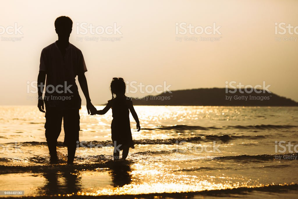 Silhouette of asian father and daughter holding hand and walking on the beach together stock photo