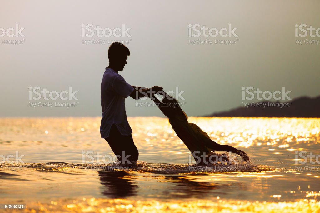Silhouette of asian father carrying his daughter turn around and playing together in the sea stock photo