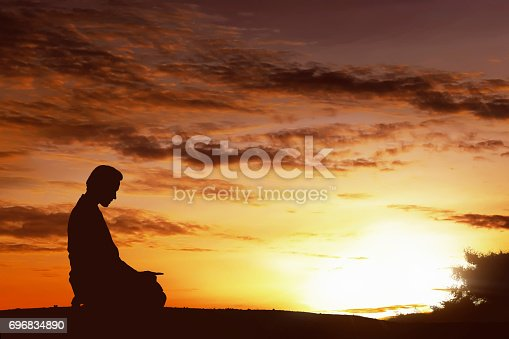 istock Silhouette of asian muslim man praying on a hilltop 696834890