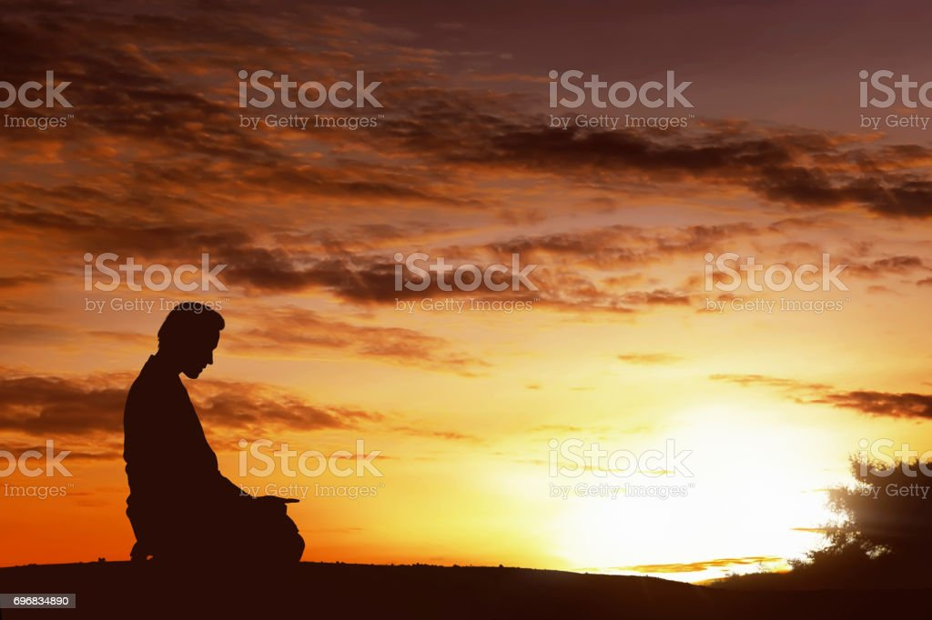 Silhouette of asian muslim man praying on a hilltop stock photo