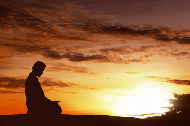 Silhouette of asian muslim man praying on a hilltop Silhouette of asian muslim man praying on a hilltop at sunset alternative pose stock pictures, royalty-free photos & images