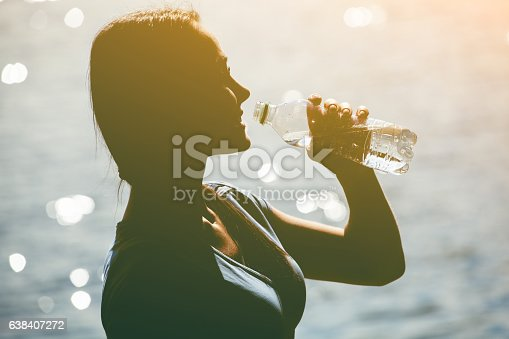 638628530 istock photo Silhouette of athlete drinking water from bottle. 638407272