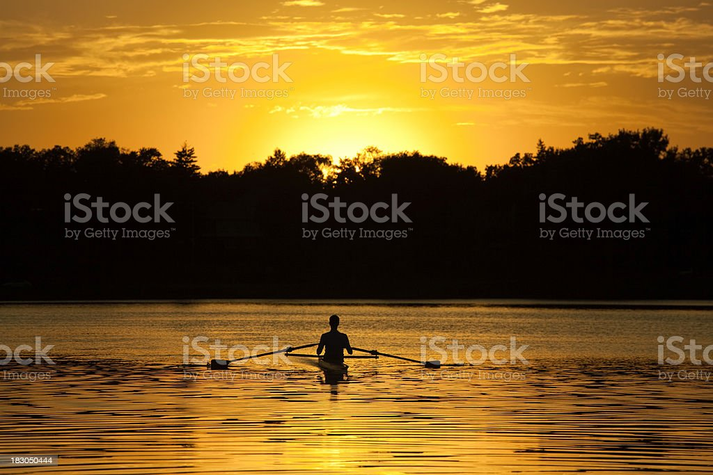 Silhouette of Athlete in rowboat on Lake in Sunset stock photo