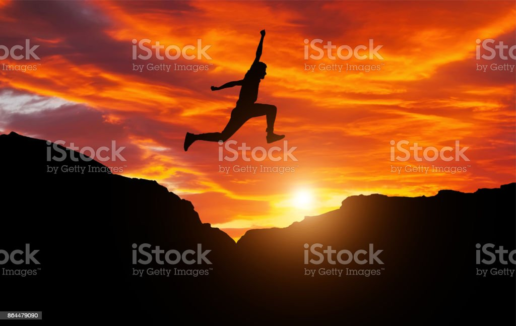 Silhouette of athlete, jumping over rocks in mountain area against sunset. Training running and jumping in difficult conditions in a beautiful nature with cloudy sky stock photo