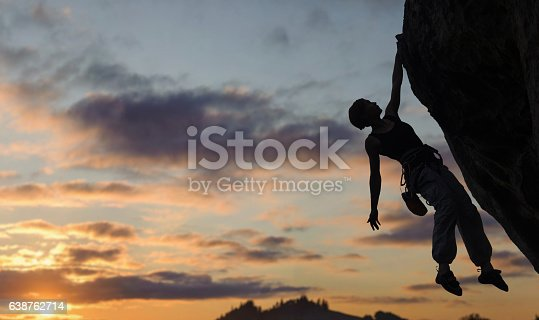 istock Silhouette of athletic woman climbing steep rock wall 638762714