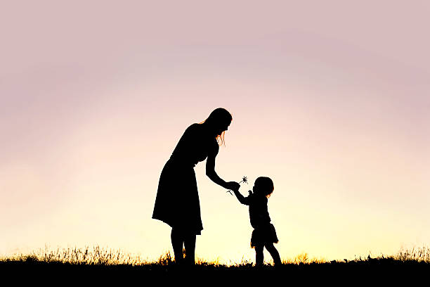 Silhouette of Baby Girl Giving Mom Flower at Sunset stock photo
