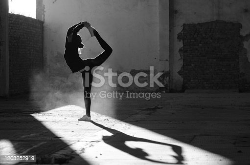 Silhouette of ballerina dancing in an abandoned building on a sunny day in black and white.