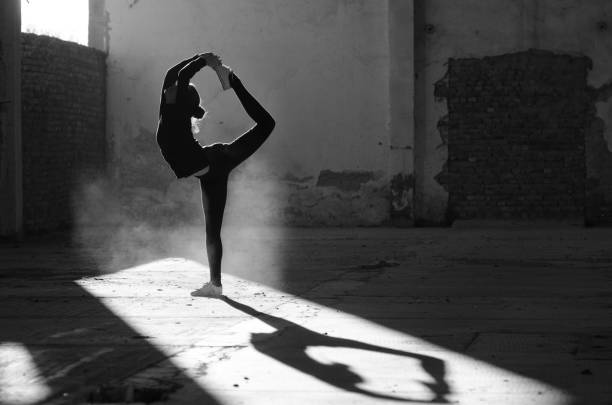 Silhouette of ballerina dancing in abandoned building stock photo