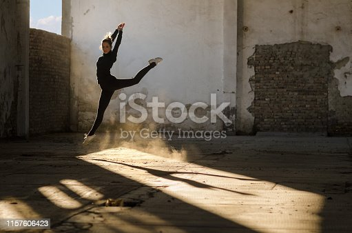Silhouette of young beautiful ballerina dancing in an abandoned building.