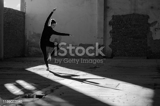 Silhouette of ballerina dancing in an abandoned building on a sunny day.