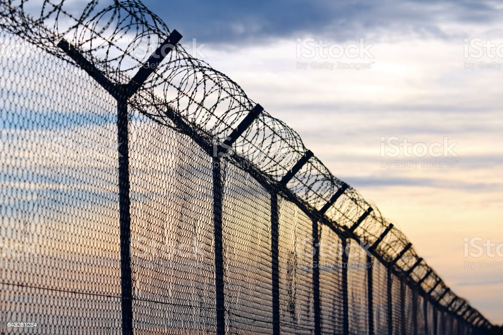 Silhouette of Barbed Wire fence against a Cloudy Sky Silhouette of Barbed Wire fence against a Cloudy Sky Backgrounds Stock Photo