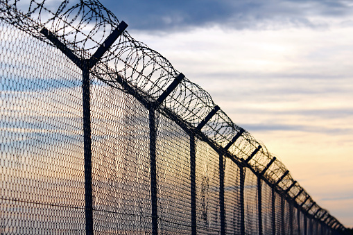 istock Silhouette of Barbed Wire fence against a Cloudy Sky 643281234