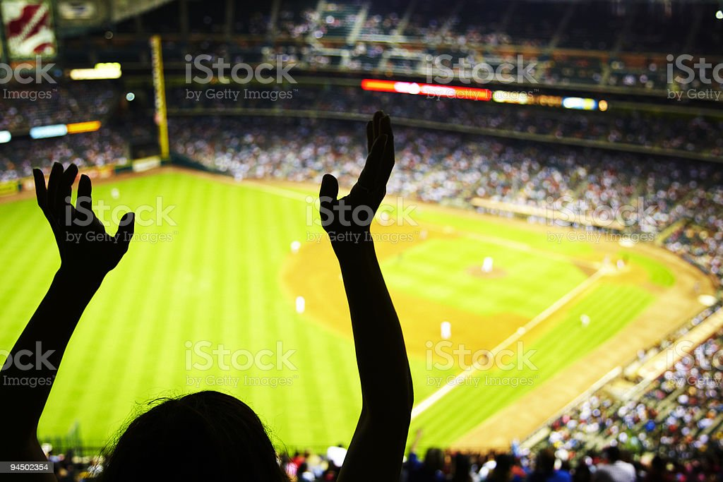 Silhouette of Baseball fan waving hands in the air stock photo