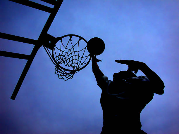 Silhouette of basketball player shooting a hoop Stunning silhouette of basketball player and hoop against deep blue sky.  If there was one shot he could make, it was a finger roll. jump shot stock pictures, royalty-free photos & images