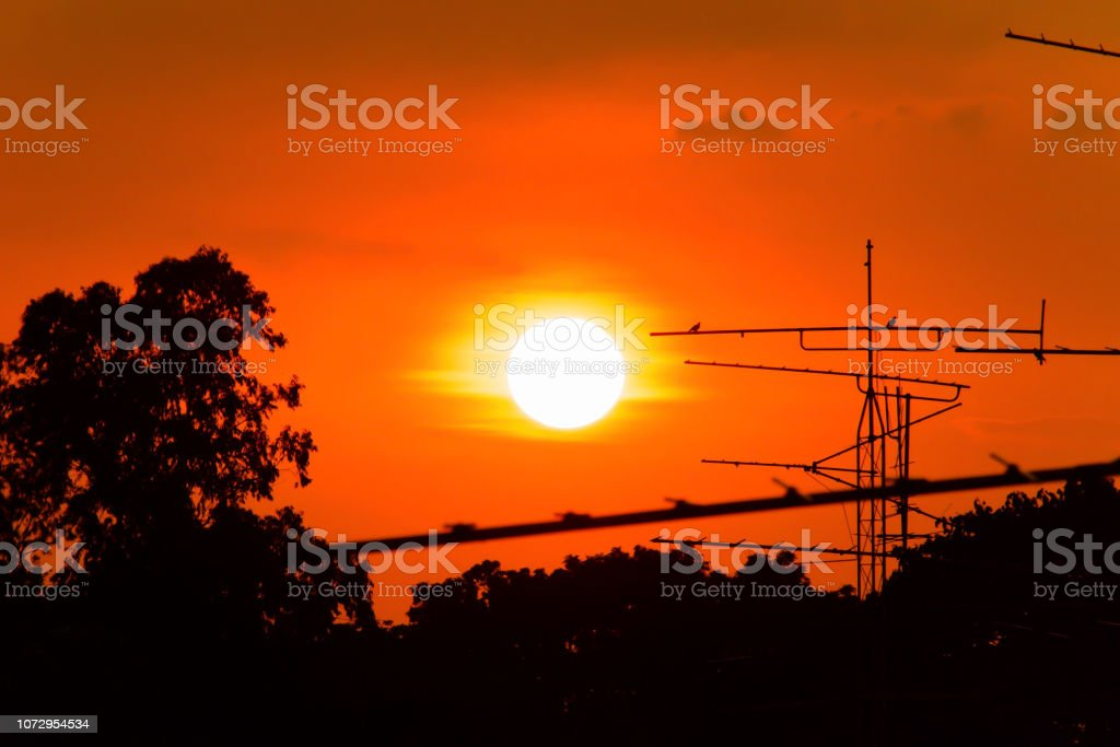 Silhouette of Beautiful sunset with television antenna or...