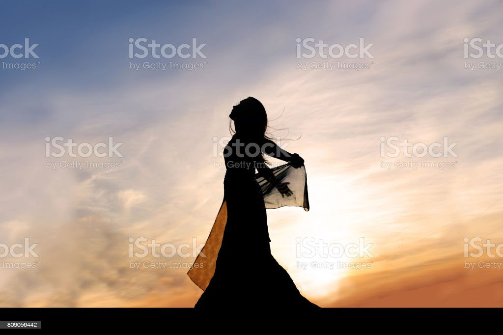 Silhouette of Beautiful Young Woman Outside at Sunset Praising God stock photo