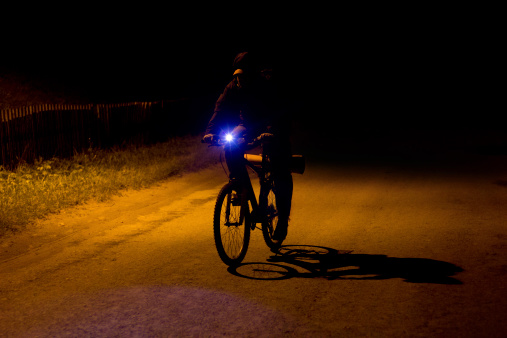 silhouette of bicyclist is at night on the road