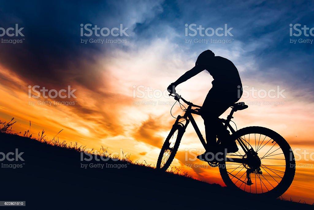 silhouette of biker boy riding mountain bike on hills stock photo