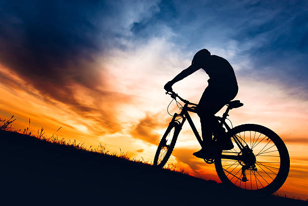 silhouette of biker boy riding mountain bike on hills - mountain bike stock pictures, royalty-free photos & images