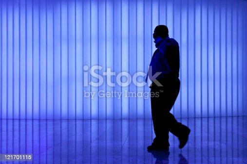 905689676 istock photo silhouette of black business man against blue modern light wall 121701115