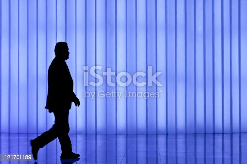905689676 istock photo silhouette of black business man against blue modern light wall 121701189