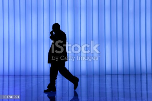 905689676 istock photo silhouette of black business man against blue modern light wall 121701201