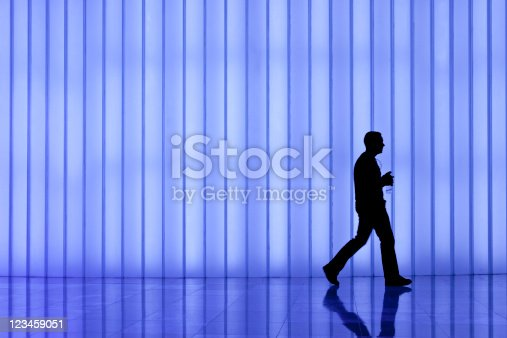 905689676 istock photo silhouette of black business man against blue modern light wall 123459051